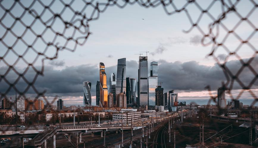 A view of the skyline of Moscow, as seen through a hole in a chain-link fence.