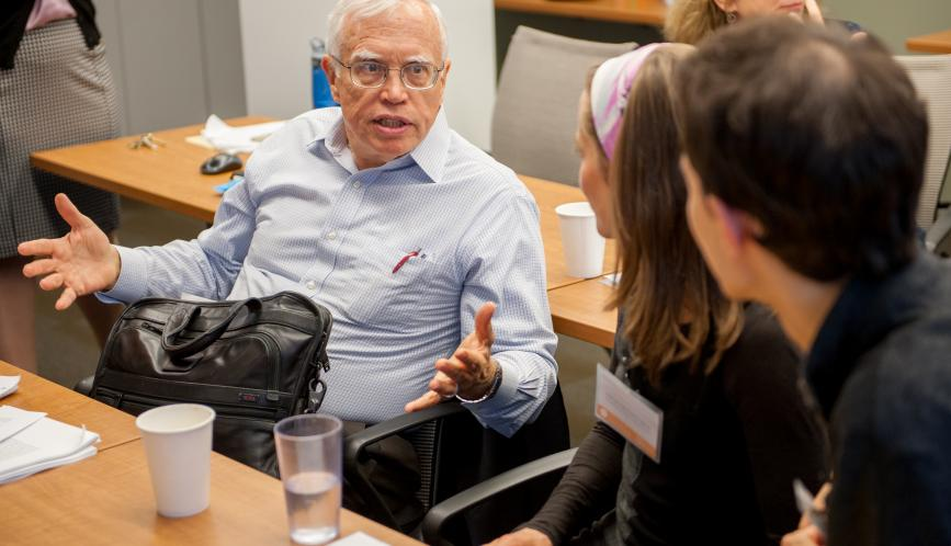 James Heckman, seated, in conversation with conference attendees.