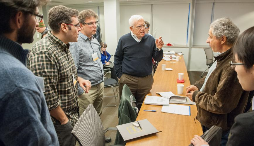 James Heckman in conversation with a group of conference attendees.