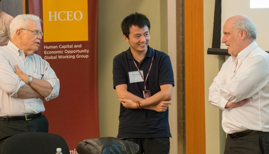 James Heckman, Wei Huang, and Steven Durlauf standing at the front of the classroom.