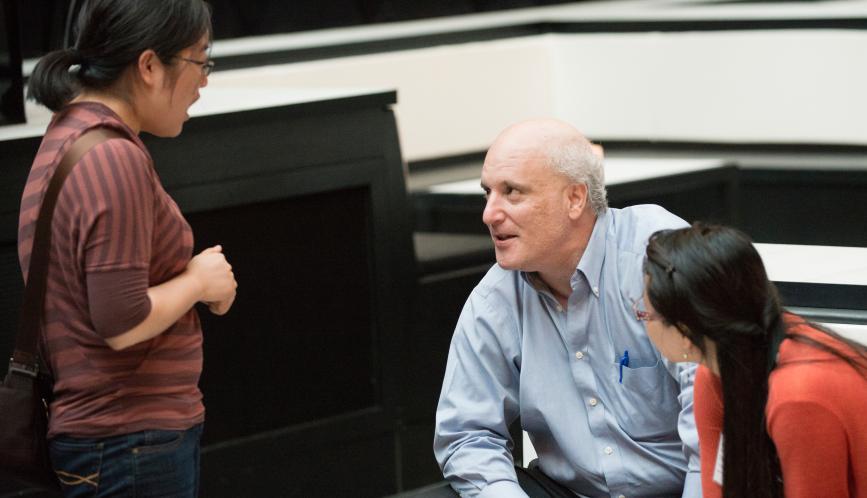 Steven Durlauf, seated, in conversation with summer school students.