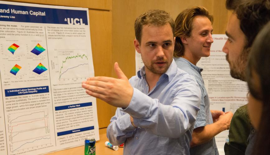 A student presents his research to another student during poster sessions.