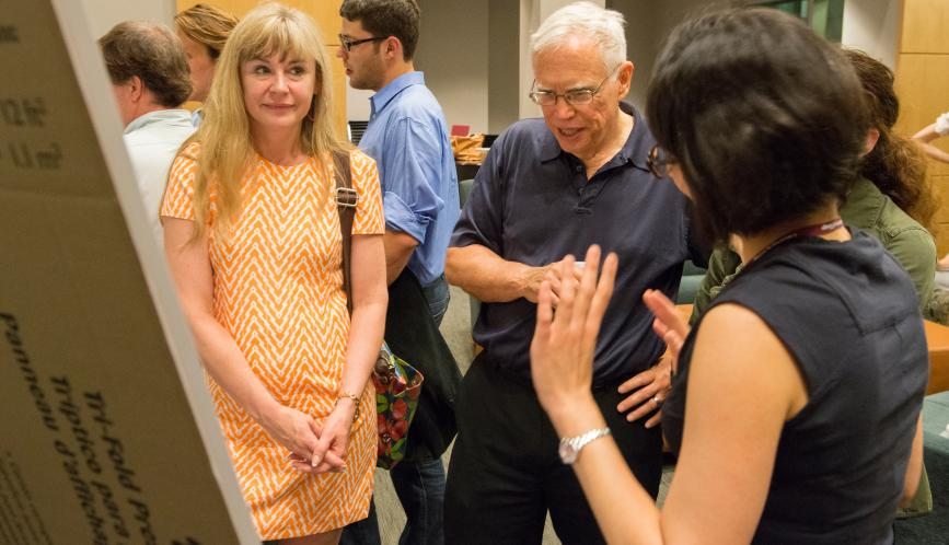 James Heckman, Petra Todd, and Gabriella Conti listen to a student present their work during poster sessions.