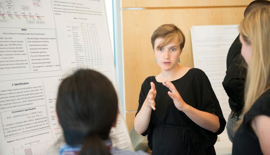 A students presents her work to other students during poster sessions.