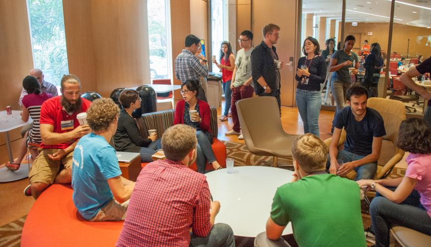 A room of summer school students in conversation during a break.