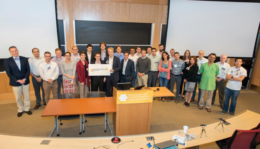 A group photo of all the conference attendees standing in front of the blackboard.