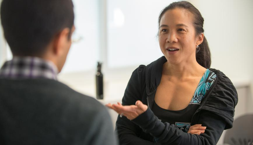 Angela Duckworth speaking with someone who has their back turned to the camera.