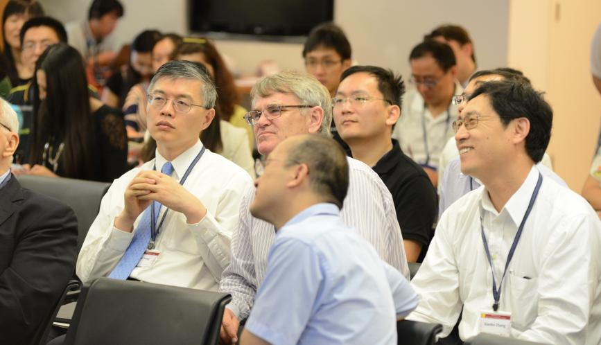 Dali Yang and other attendees listening to a presentation