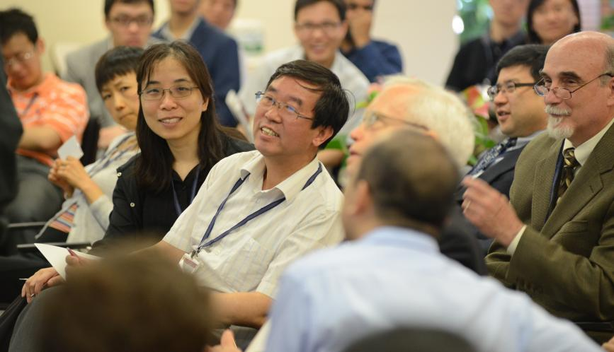 A group of conference attendees smiling in the audience