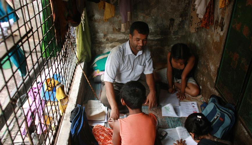 Stock image of a family sitting in a small concrete room doing homework.