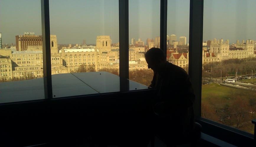 Someone in silhouette standing at the window, with the University of Chicago campus seen through the windows.