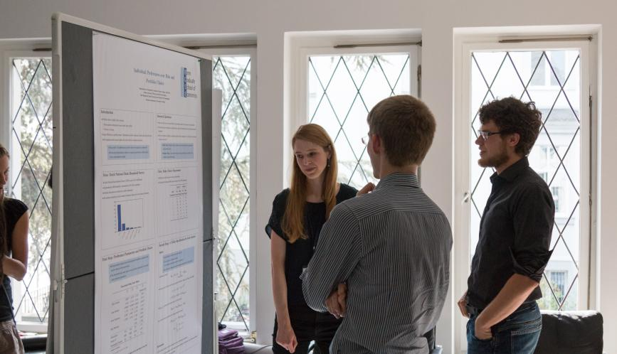 Students look at a student's work during poster sessions.