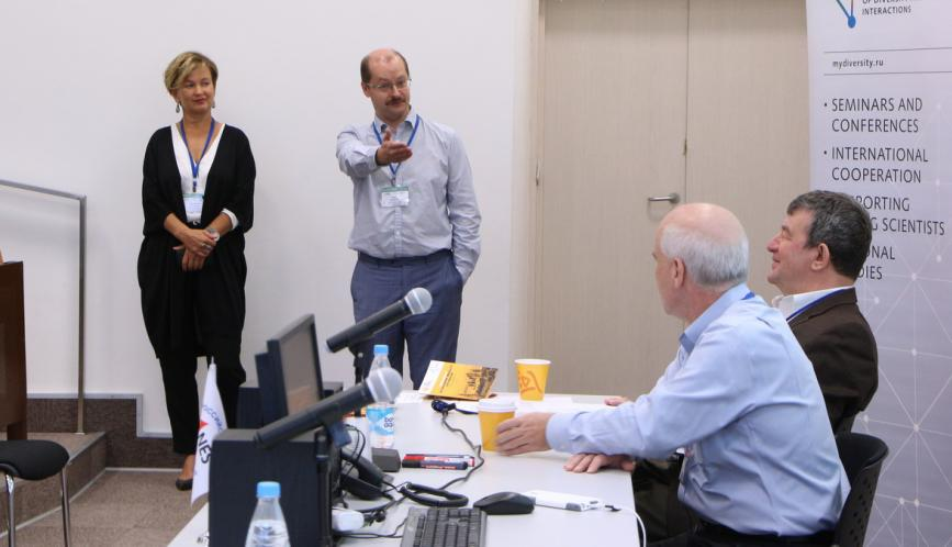 Steven Durlauf and Shlomo Weber seated at the front of the room, while two summer school attendees stand in conversation.