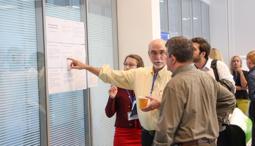 Larry Blume discusses a student's research during poster sessions.