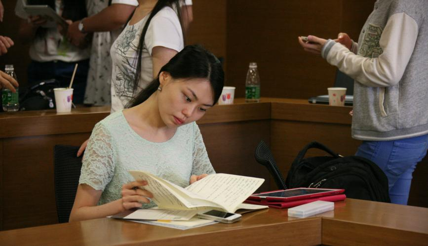 A student sitting and looking at a notebook.