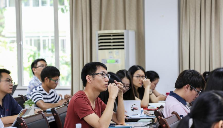 Students, seated in the classroom, listening to a presenter.