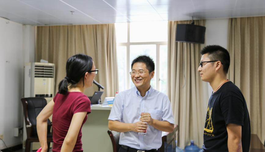 Shuaizhang Feng speaking to two students.