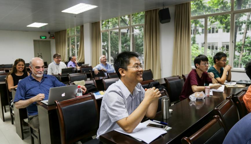 Shuaizhang Feng, smiling, seated at the front of the summer school classroom.