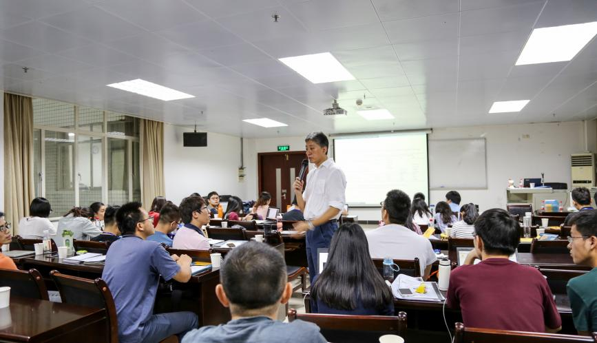 James Kung, standing in the middle of the classroom, speaking to students.