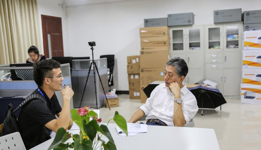 James Kung, seated, speaking to a student.