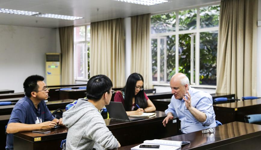Steven Durlauf, seated, speaking with three seated students.