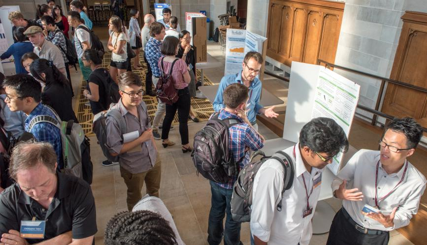 An overhead image of a room of students and faculty in conversation during poster sessions.