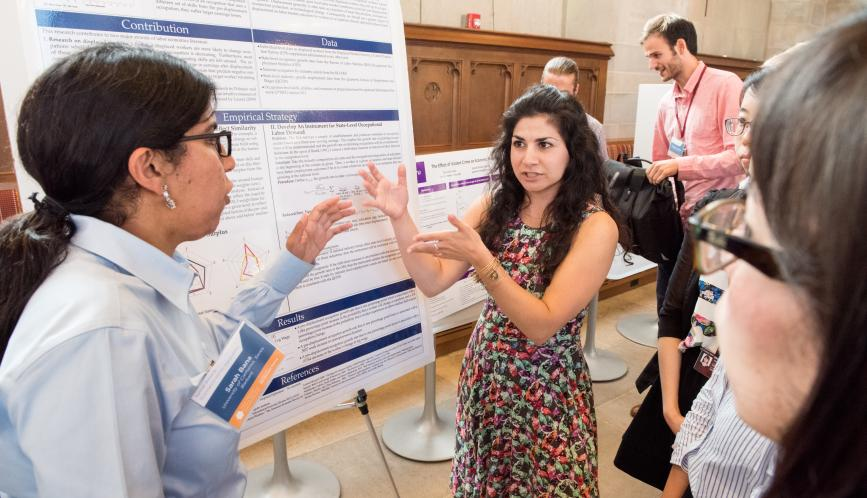 A student presents her work to other students during poster sessions