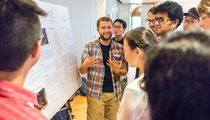 A group of students listen as another student presents his poster.