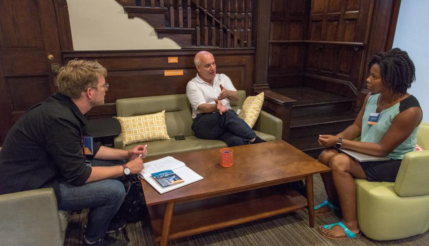 Steven Durlauf meets with two students during office hours.