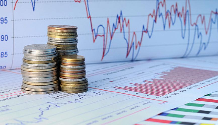 A stock image of three stacks of coins sitting amid colorful graphs and charts.