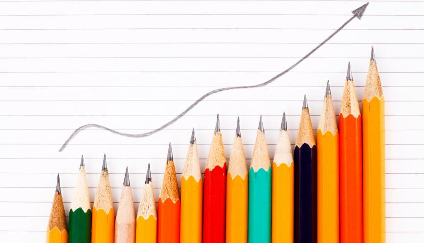 A stock image of different colored pencils, arranged in an escalating fashion, while a drawn arrow points upwards on a piece of paper behind them.