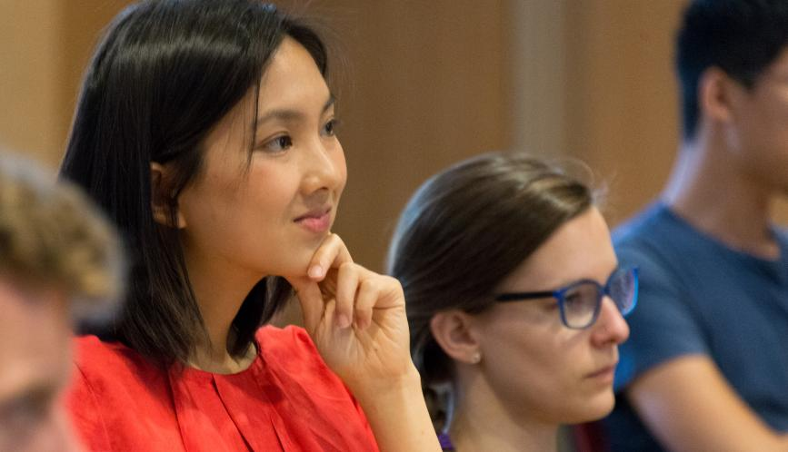 A student listens to a lecture, smiling.