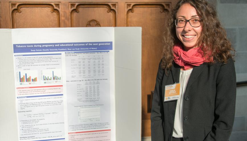 A summer school student standing in front of her research during poster sessions.