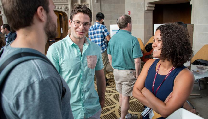 Students stand in conversation during poster sessions.
