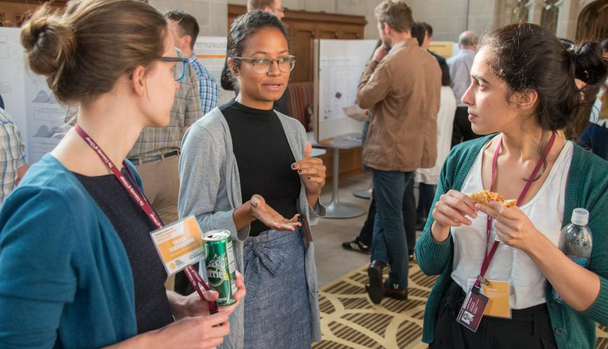 Three students stand in conversation during poster sessions.