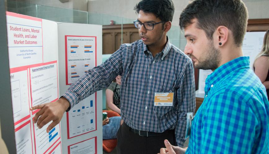 A student presents hris work during poster sessions, while another student listen.