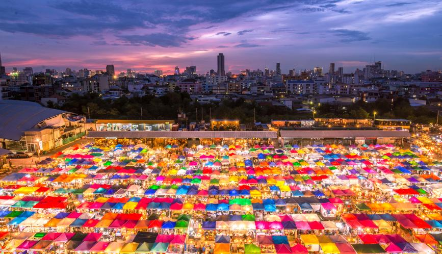 An image of a night market showing illuminated, multi-colored tents.