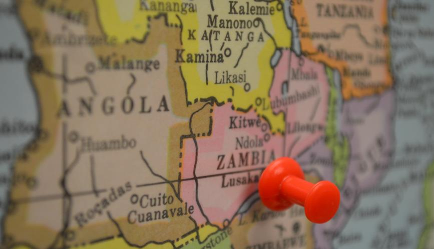 A picture of a map of Zambia, with a red thumbtack stuck into it.