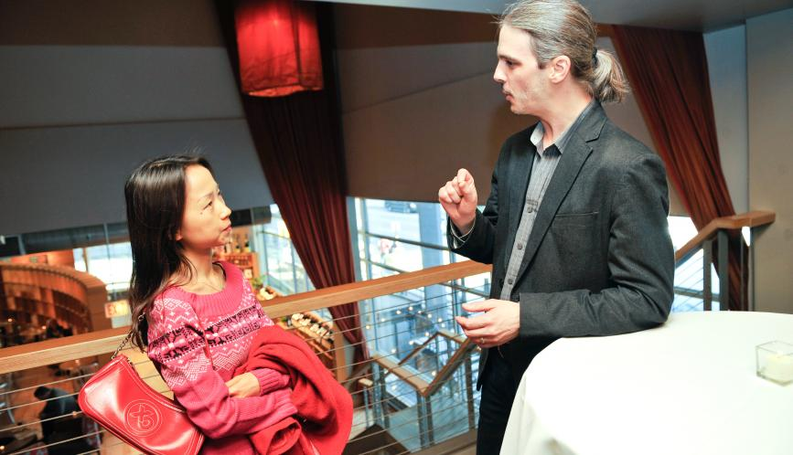 Chao Fu in conversation with another conference attendee.
