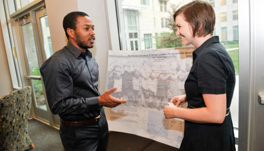 Two students in conversation during poster sessions.