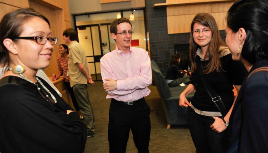 Scott Kominers talking to three students.
