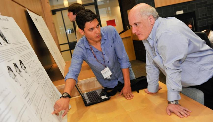 A student explains his work to Steven Durlauf during poster sessions.