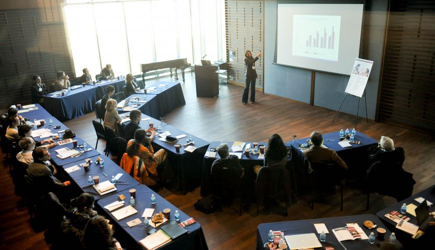 Aerial view of the conference room, with attendees watching a lecture.