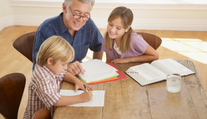 A grandfather helping two grandchildren study at the kitchen table.