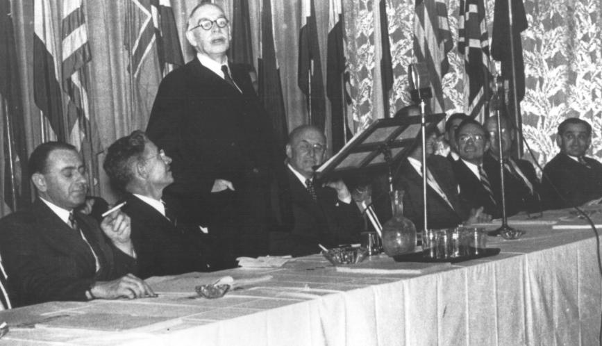 A black and white photo showing John Maynard Keynes standing at a formal event table