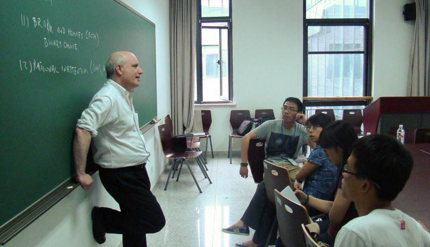 Steven Durlauf standing in front of a chalkboard, in conversation with a group of students sitting at desks in a classroom.