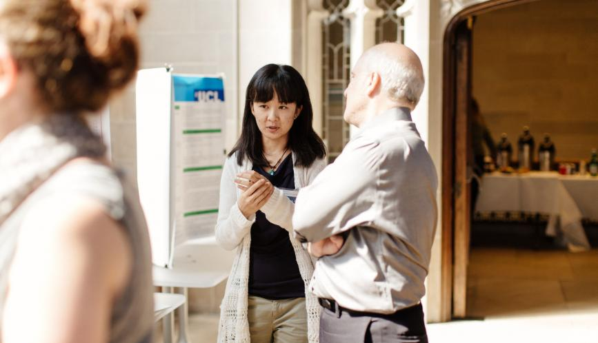 Xuejing Zuo speaks with Professor Steven Durlauf about her poster during a poster session on campus.