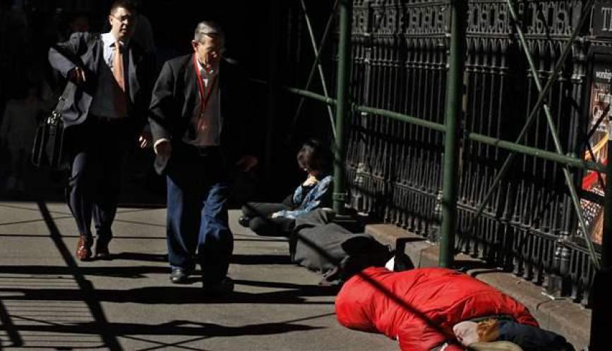 Men walking past houseless person sleeping on the street