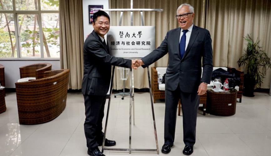 James J. Heckman and Shuaizhang Feng shaking hands.