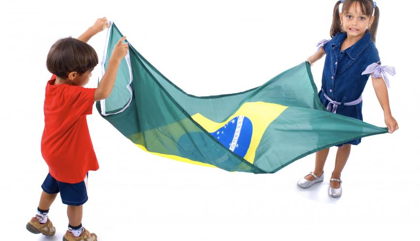 Two young children holding the Flag of Brazil